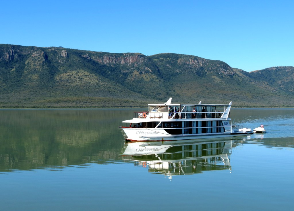 A house boat cruising on Kake Kariba with the Matusadona mountain range in the background